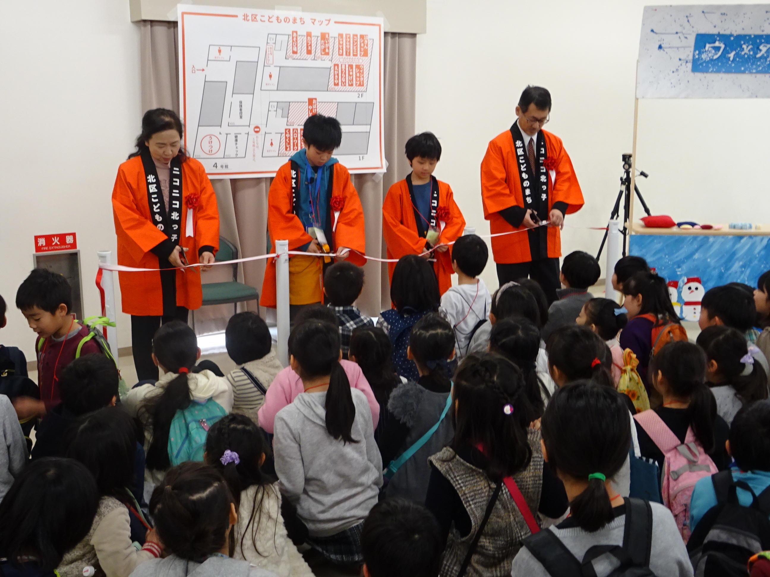 「北区こどものまち」を大谷大学で開催。仮想の「まち」を舞台に、京都市北区の約200名の子どもたちが楽しみながら社会の仕組みを体験。教育学、社会学を学ぶ学生が学科を超えて協力・サポート